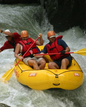 three people on whitewater raft in Costa Rica
