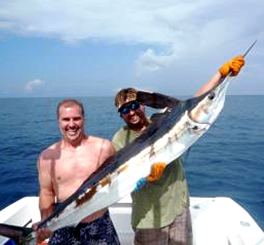 two men with a white marlin while fishing