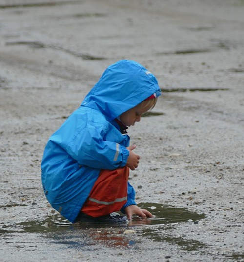 child playing with a puddle in the rain in Costa Rica