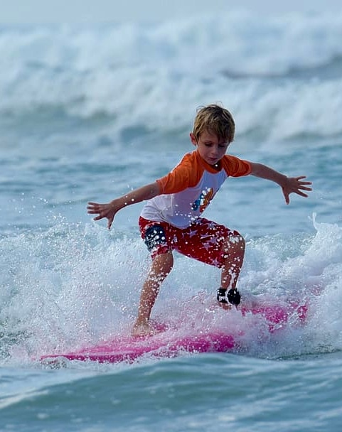 kid on a surfboard in costa rica near los suenos