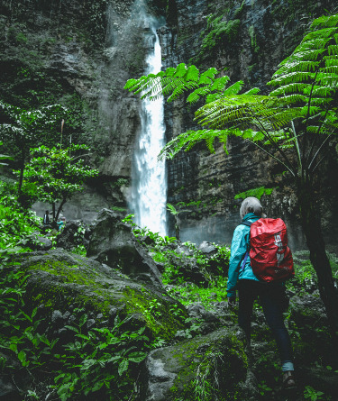 woman at a waterfall on a hike in Costa Rica